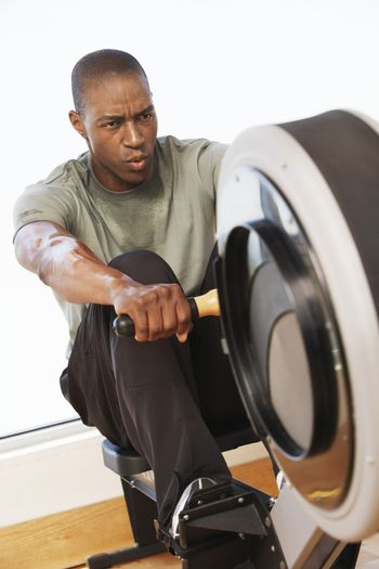 Young African American man working out on rowing machine in health club