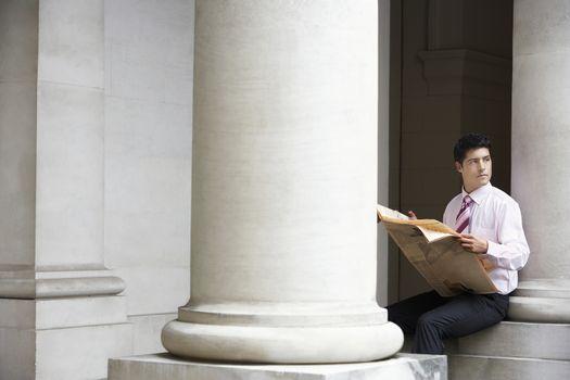 Businessman sitting on pillar under entablature reading newspaper