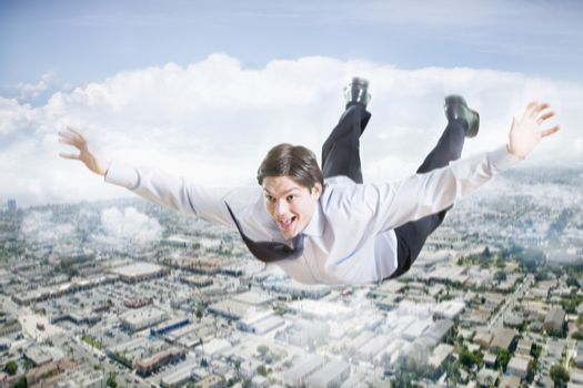 Conceptual image of excited businessman flying in the clouds