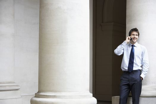 Happy young businessman using mobile phone by building pillar