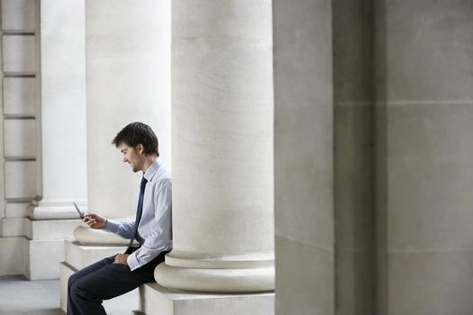 Side view of businessman reading text message while sitting against building pillar