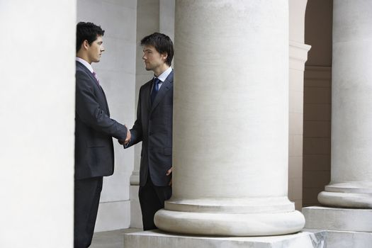 Smiling young businessmen shaking hands by building pillar