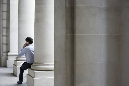 Rear view of businessman using mobile phone while sitting against building pillar