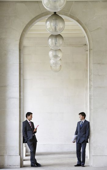 Young businessmen conversing at archway