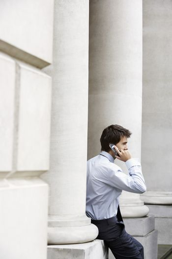 Side view of young businessman using mobile phone by pillar