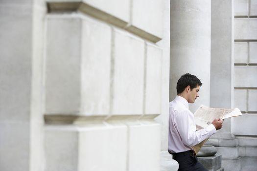 Businessman sitting on pillar reading newspaper outside building
