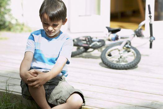 Sad little boy sitting on porch of house