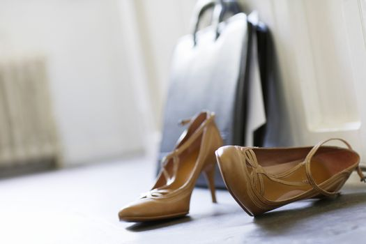 Closeup of high heels and briefcase on floor