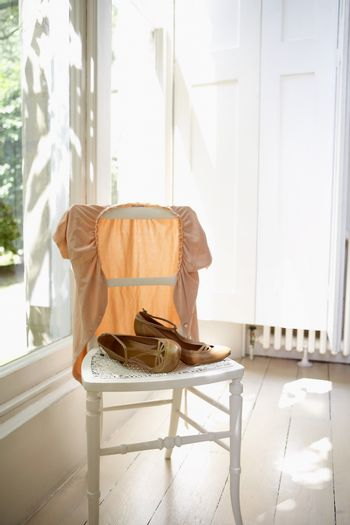 Female jacket and shoes on chair by window