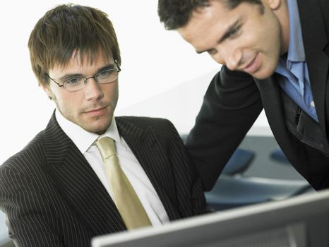 Young businessmen looking at computer in office