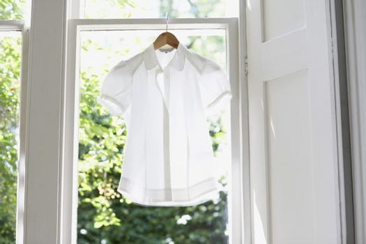 Blouse on hanger at domestic window