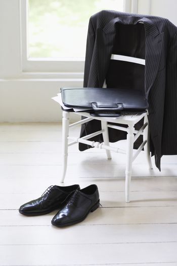 Business suit, case and formal shoes at home