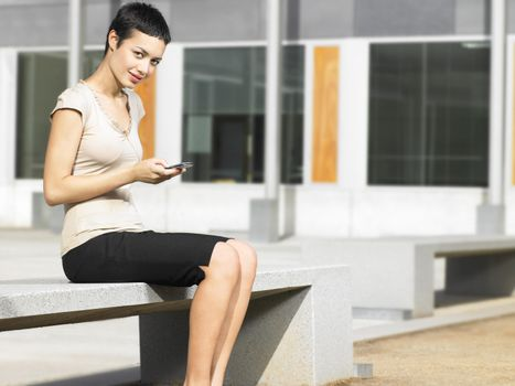 Portrait of confident young businesswoman holding cell phone in plaza