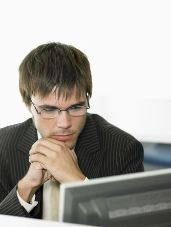 Serious young businessman looking at computer in office