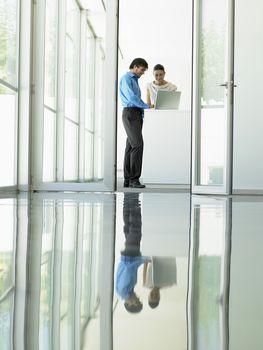 Businessman and businesswoman using laptop in meeting viewed through open office door