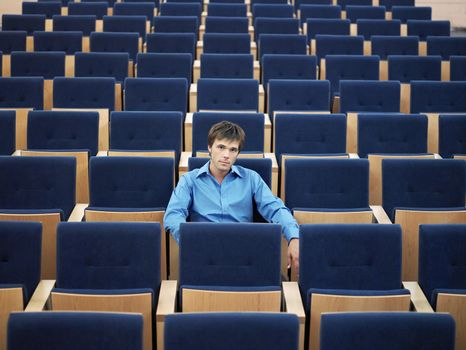 Portrait of young businessman sitting alone in auditorium