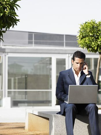 Young businessman on call while using laptop in plaza