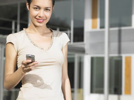 Portrait of young businesswoman text messaging outside office