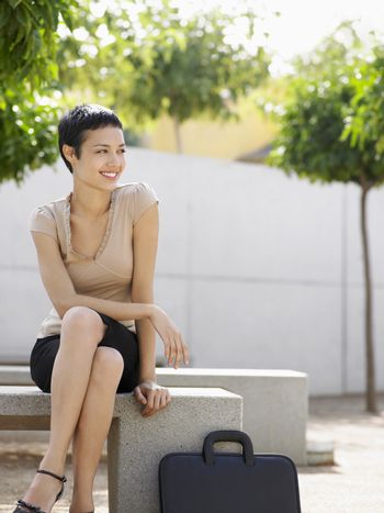 Smiling young businesswoman sitting on bench in plaza