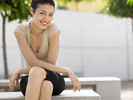 Portrait of smiling young businesswoman sitting on bench in plaza
