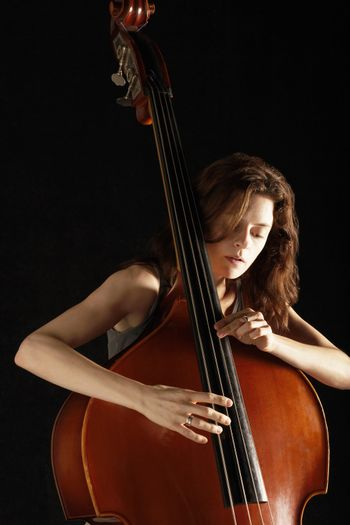 Young woman playing double bass against black background