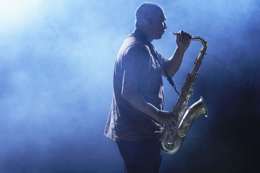 Man Playing Saxophone in smoky place side view