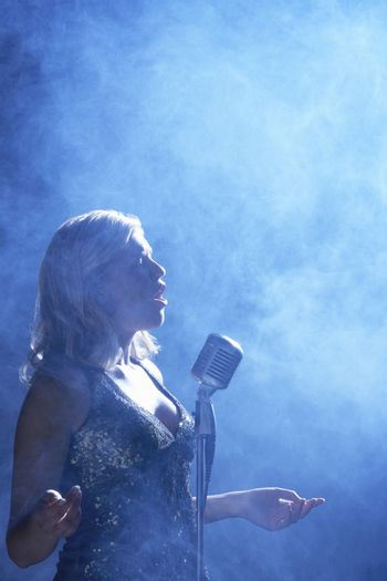 Side view of a young woman singing at microphone in smoky place