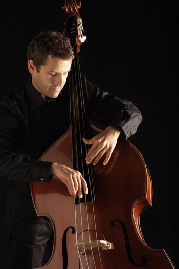 Young man playing double bass against black background