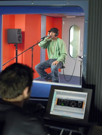 Young male singer with studio technician in foreground at the recording studio