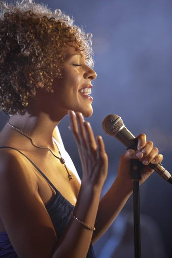Closeup profile of a happy female jazz singer on stage