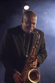 Jazz musician playing saxophone on smokey stage