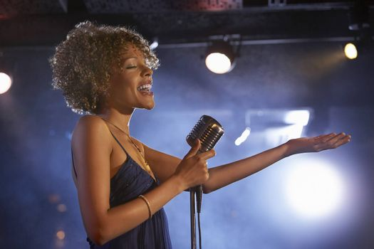 Profile shot of a happy female jazz singer on stage
