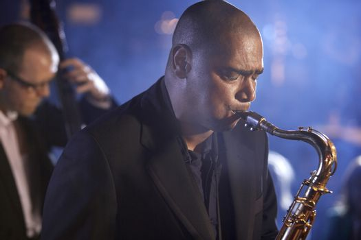 Saxophone player with man playing double bas in background on stage