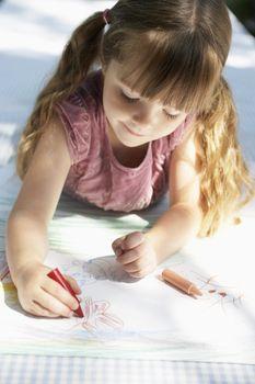 Young girl lying on backyard table and drawing