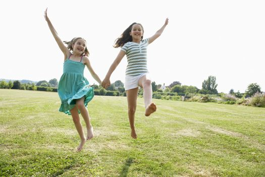 Two girls running and jumping hand in hand through field