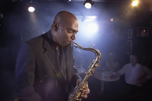 Side view of a musician playing saxophone in jazz club