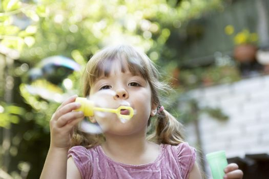 Closeup of a little girl blowing soap bubbles in the backyard