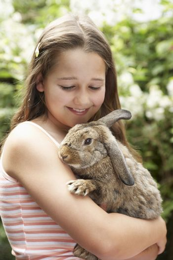 Happy young girl holding bunny rabbit in the backyard