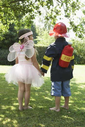 Rear view of a girl and boy dressed as fairy and fireman in park