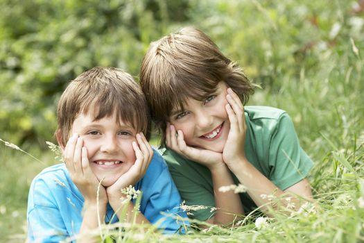 Portrait of two happy boys lying side by side in grass