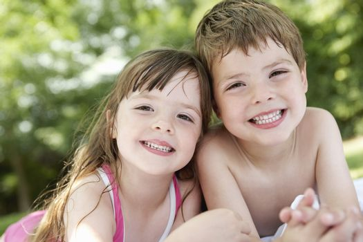 Closeup portrait of a boy and girl lying in the backyard