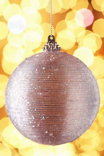 Closeup of Christmas bauble over colored background