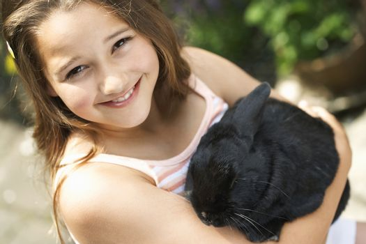 Portrait of a happy young girl holding bunny rabbit in the backyard