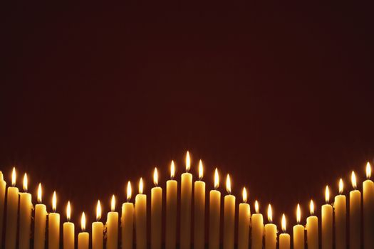 Row of lit candles on black background