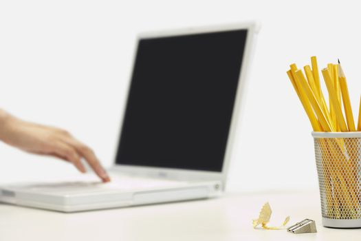 Pencils and sharpener by person using laptop on white background