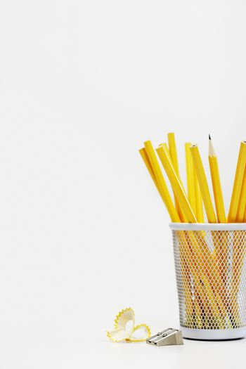 Group of yellow pencils in holder by sharpener over white background