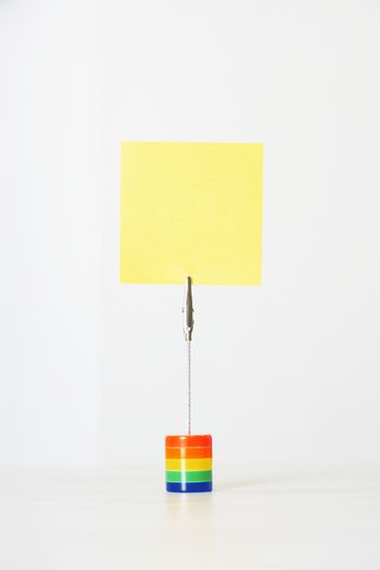 Closeup of a blank sticky notepaper with holder against white background