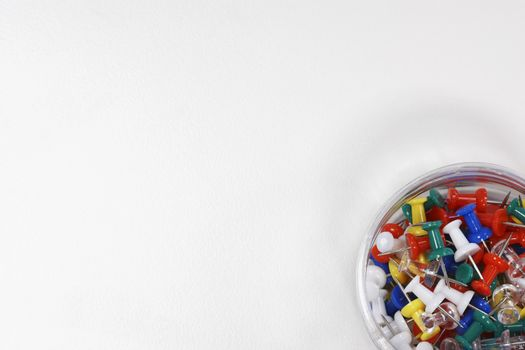 Container of push pins over white background