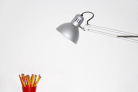 Angle poise lamp and pencil holder over white background