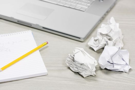Crumpled papers and notebook on desk by laptop